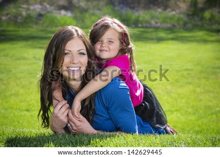Mother and daughter having fun together outdoors - stock photo
