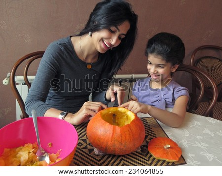 Mother and Daughter Having Fun While Carving a Halloween Pumpkin. - stock photo