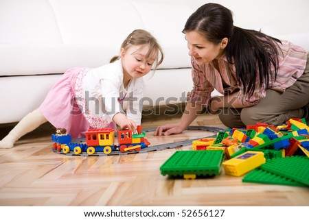mother and daughter having fun with bricks at home - stock photo