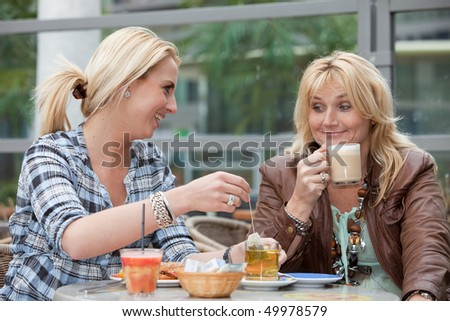 Mother and daughter having lunch together outside