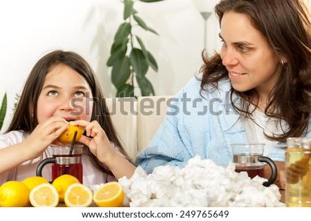 Mother and daughter having tea, eating lemon, honey to heal - stock photo