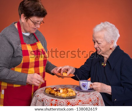 Mother and daughter having tea with apple pie on an orange  background - stock photo