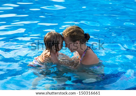 Mother and daughter head to head having passionate great time in the swimming pool.