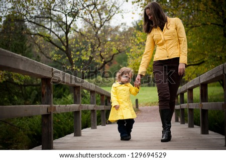 Mother and daughter holding hands go on the bridge - stock photo