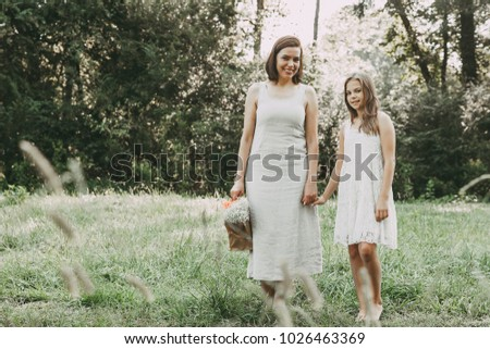 Mother and daughter holding hands in natural environment.