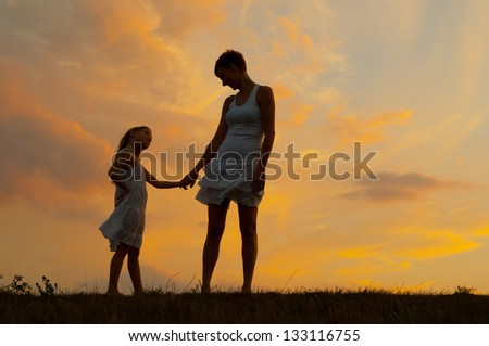 Mother and daughter holding hands in the nature. - stock photo