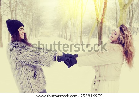 mother and daughter holding hands in the snow - stock photo