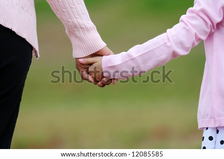 Mother and daughter holding hands while walking together - stock photo