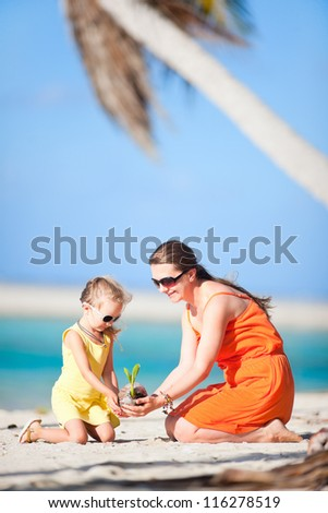Mother and daughter holding small coconut sprout at beach