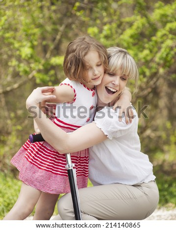 Mother and daughter hug in park with scooter - stock photo