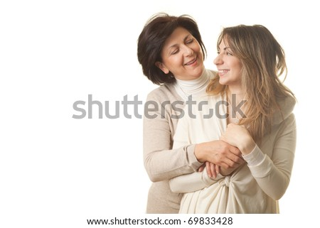 Mother and daughter hugging and smiling against white background