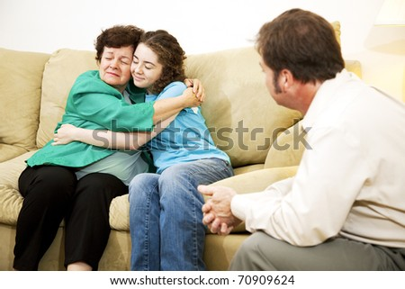 Mother and daughter hugging during a family counseling session with a therapist. - stock photo
