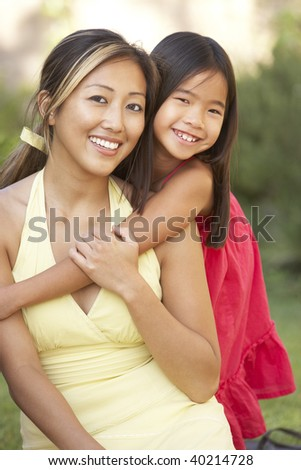 Mother And Daughter Hugging In Garden - stock photo