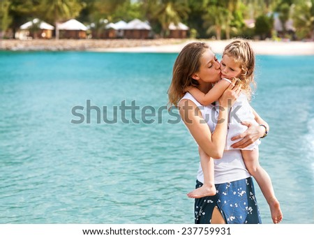 mother and daughter hugging in love on the sea resot  - stock photo