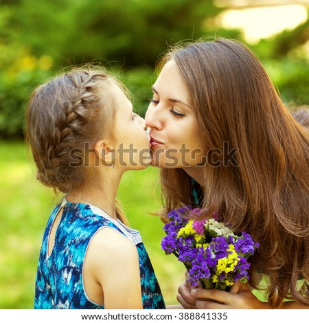 mother and daughter hugging in love playing in the park. Mothers day.