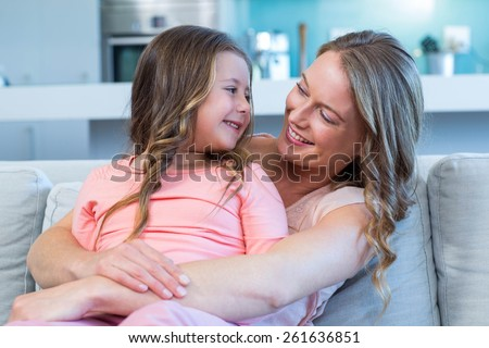 Mother and daughter hugging on couch at home in the living room - stock photo