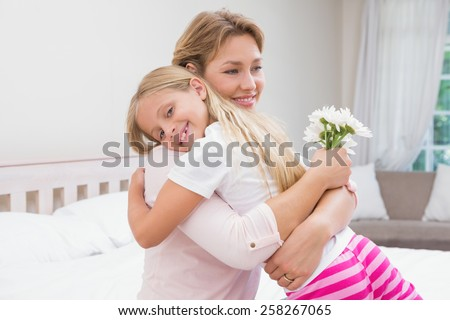 Mother and daughter hugging with flowers at home in the bedroom - stock photo
