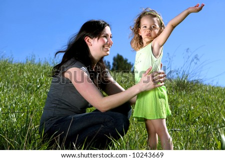 Mother and daughter in a field - stock photo