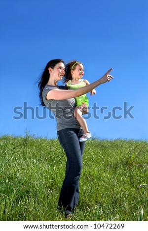 Mother and daughter in a meadow, pointing