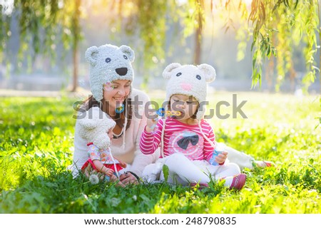 mother and daughter in a park wearing a knit hat. - stock photo