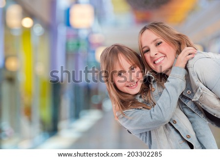 mother and daughter in a shopping center - stock photo