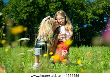 Mother and daughter in a sunlit meadow with lots of flowers, hugging each other