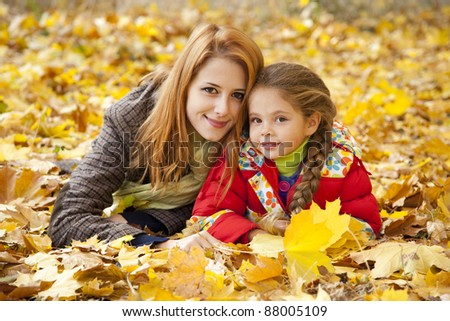 Mother and daughter in autumn yellow park. - stock photo