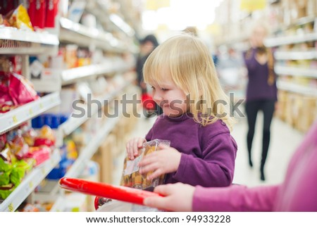 Mother and daughter in bakery section of supermarket. Daughter with cookies - stock photo