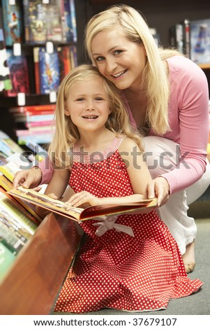Mother and daughter in bookshop - stock photo