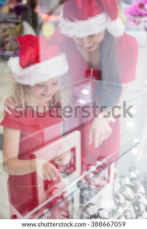 Mother and daughter in Christmas attire looking at wrist watch display in shop - stock photo