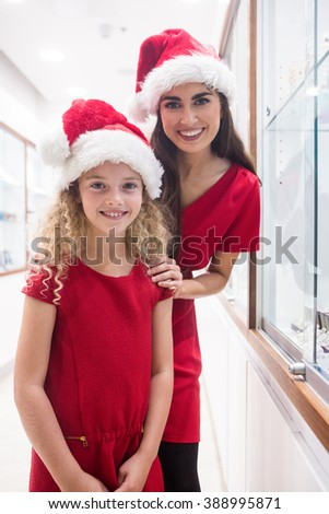 Mother and daughter in Christmas attire standing in a jewelry shop in shopping mall - stock photo