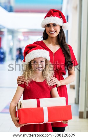Mother and daughter in Christmas attire standing in shopping mall with Christmas gifts - stock photo