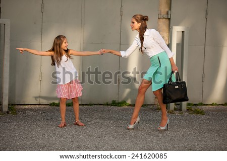 Mother and daughter in city in late summer afternoon - stock photo