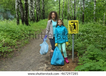 Mother and daughter in city to clean up forest, in hands of bags of garbage