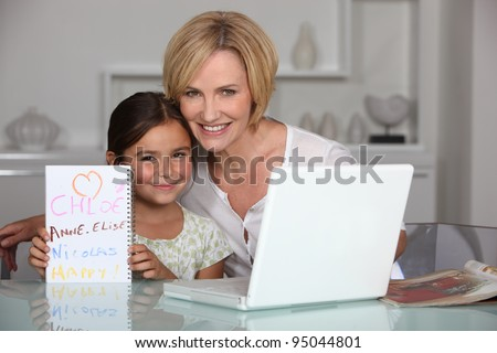 Mother and daughter in dining room with laptop