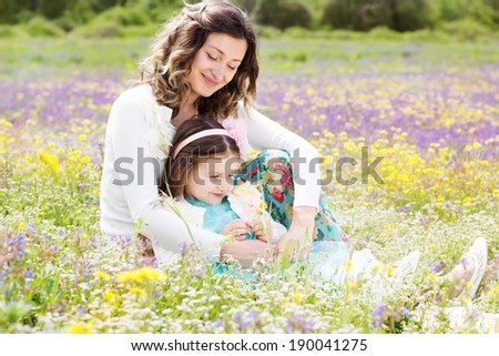 Mother and daughter in field with colorful flowers - stock photo