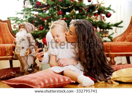 Mother and daughter in front of Christmas tree,playing on phone taking selfie. Shallow depth of field - stock photo