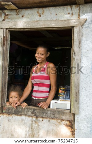 mother  and daughter in front of clapboard house in Big Corn Island Nicaragua Central America - stock photo