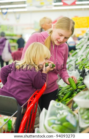 mother and daughter in fruit and vegetables section in supermarket - stock photo