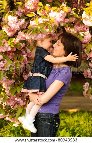 Mother and daughter in garden, under the sakura tree. Spring. - stock photo