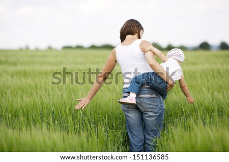 mother and daughter in green field - stock photo