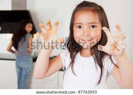 Mother and daughter in kitchen, child looking at camera with cookie dough on hands - stock photo