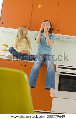 Mother and daughter in kitchen, mother juggling oranges