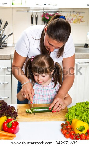 Mother and daughter in kitchen preparing vegetables - stock photo