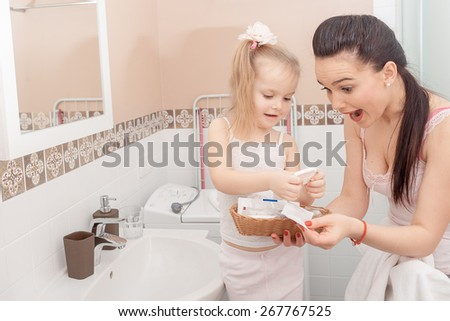 Mother and daughter in modern interior bathroom - stock photo