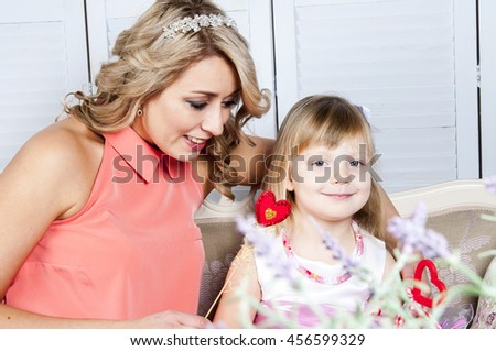 Mother and daughter in provence style interior - stock photo