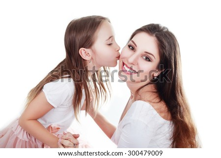 mother and daughter in same outfits posing on studio kissing - stock photo