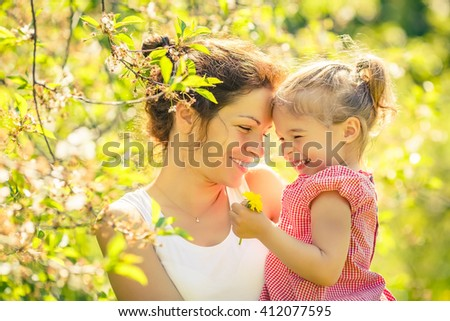Mother and daughter in spring sunny park - stock photo
