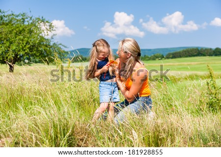 Mother and daughter in sunlit meadow hugging each other - stock photo