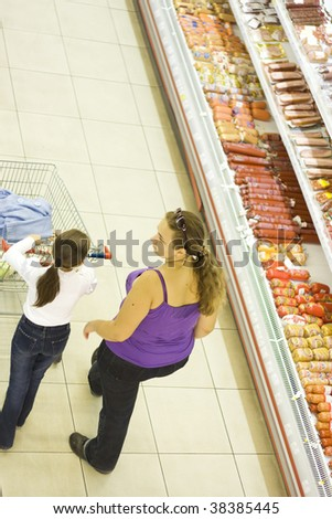 Mother and daughter in supermarket. Shopping